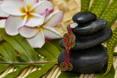 plumerias: Smooth black rocks stacked with feng shui chinese coins for good luck on fern leaf and bamboo mat with plumerias