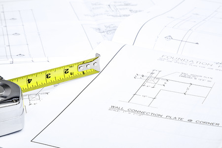 leather gloves: A set of blueprints with a tape measure sitting on them Stock Photo