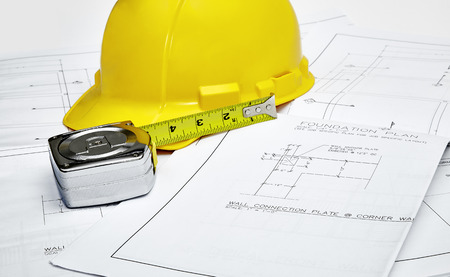 hardhat: A set of blueprints with hardhat and tape measure Stock Photo