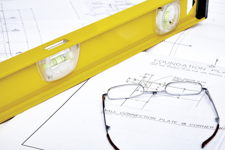 leather gloves: A set of blueprints with  reading glasses and a yellow level