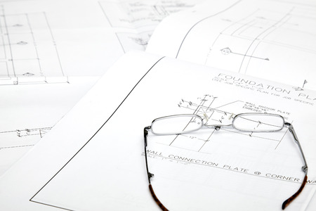 leather gloves: Blueprints with reading glasses sitting on top Stock Photo