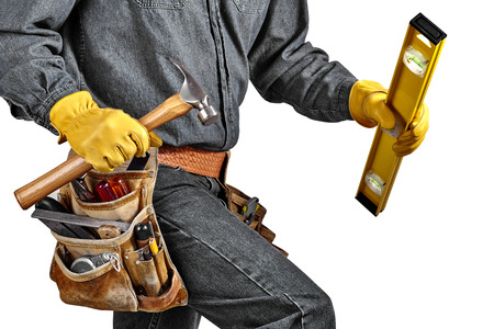 hardhat: Man in black denim wearing used tool belt filled with carpenter tools carrying a yellow level, hardhat and hammer Stock Photo