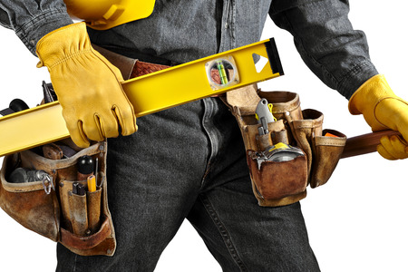 Man in black denim wearing used tool belt filled with carpenter tools carrying a yellow level, hardhat and hammer photo