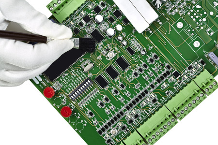 Circuit board with hand in white glove holding brush cleaning the board isolated on white photo