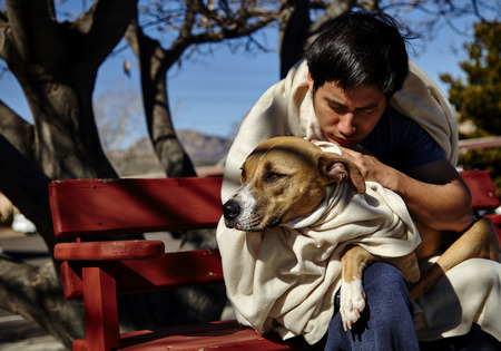 bent over: Man with dog wrapped in blanket sitting on bench bent over dog