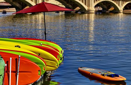 rentals: Kayak rentals stacked on dock with umbrella near bridge Stock Photo
