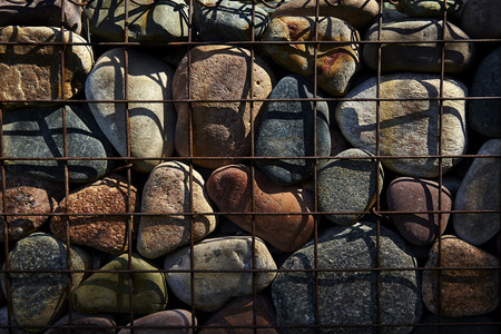 river rocks: River Rocks contained in a wire cage Stock Photo