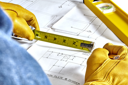 work gloves: Mans hands in leather work gloves holding a tape measure and a pencil reviewing blueprints with level laying on plans