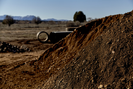 dirt pile: Pile of dirt with drain pipes and rocks in background
