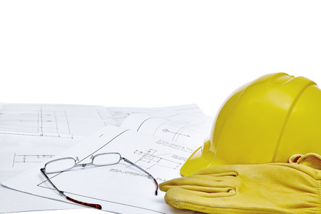 engineered: A set of blueprints with hardhat work gloves and reading glasses isolated on white