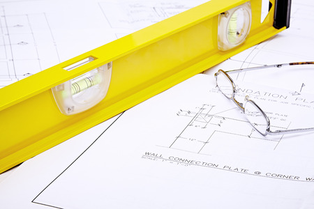 engineered: A set of blueprints with yellow level and reading glasses