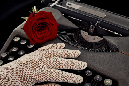crocheted: Red rose on typewriter with hand in crocheted glove