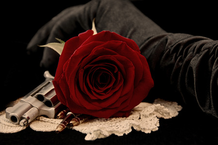 love affair: Red Rose with handgun bullets and  hand in black glove on black  Stock Photo