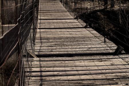 suspend: Old wooden suspension bridge with broken slats