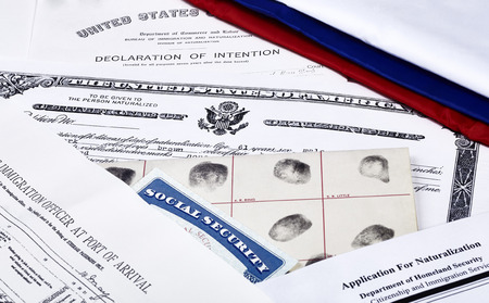 unlawful act: US Certificate of Citizenship declaration of intention fingerpirnt card social security card application for naturalization and port of arrival manifest with red white and blue ribbon