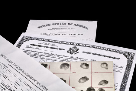 illegal alien: Certificate of US Citizenship, fingerprint card, Declaration of Intention and Passenger Manifest documents isolated on white Stock Photo