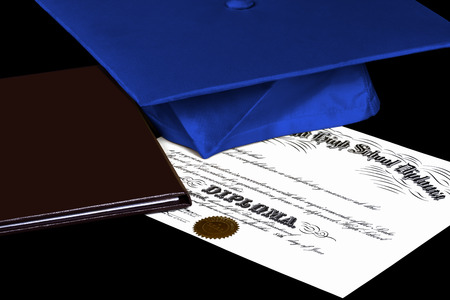 baccalaureate: High School Diploma with gold cap and leather binder isolated on black