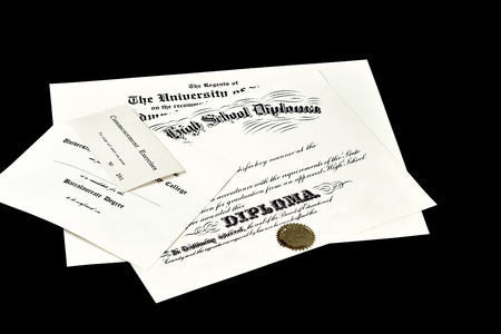 baccalaureate: Education certification documents including high school diploma,commencement ticket, and university degree isolated on black