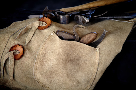 rasp: Tools of a farrier including rasp, hoof knife, chaps, hoof pick, and nippers draped over stool