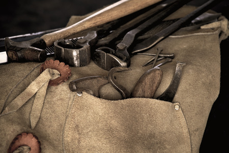 rasp: Used Tools of a farrier including rasp, hoof knife, chaps, hoof pick, and nippers draped over stool Stock Photo