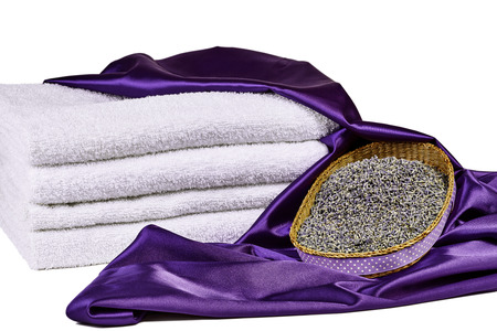spa towels: Dried lavender flowers in basket with purple satin and white spa towels isolated on white Stock Photo