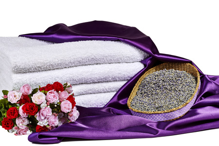 spa towels: Dried lavender flowers in basket with purple satin, red and pink roses in a bouquet and white spa towels isolated on white