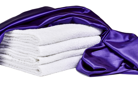 sooth: Purple satin  and white spa towels isolated on white Stock Photo