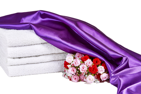 spa towels: Red and pink roses in a bouquet and white spa towels isolated on white with purple satin