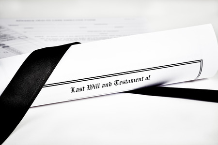 will return: Last Will and Testament rolled up with advance health care directive and tax return in background with shallow depth of field isolated on white with a black ribbon