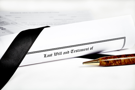 federal tax return: Last Will and Testament rolled up with advance health care directive and tax return in background with shallow depth of field isolated on white with a pen Stock Photo