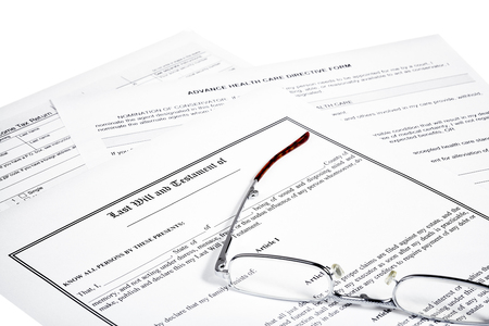 federal tax return: Last will and testament with tax return  and medical directive form with reading glasses isolated on white Stock Photo