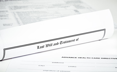 federal tax return: Last Will and Testament rolled up with advance health care directive isolated on white tax return in background with shallow depth of field Stock Photo