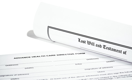 federal tax return: Last Will and Testament rolled up with advance health care directive isolated on white