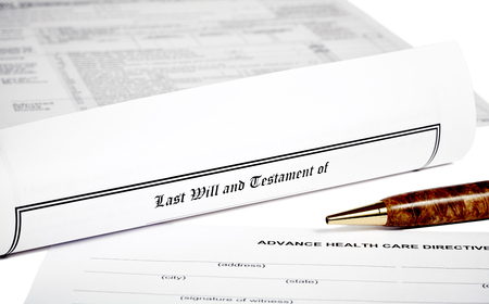will return: Last Will and Testament rolled up with advance health care directive isolated on white with a pen Stock Photo