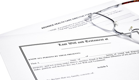 directive: Last will and testament with medical directive form and reading glasses isolated on white