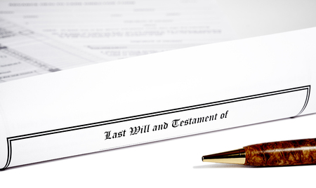 will return: Last Will and Testament rolled up with advance health care directive and tax return in background with shallow depth of field isolated on white with a pen Stock Photo