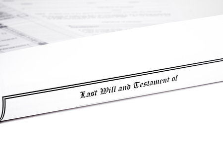 will return: Last Will and Testament rolled up with advance health care directive and tax return in shallow depth of field isolated on white