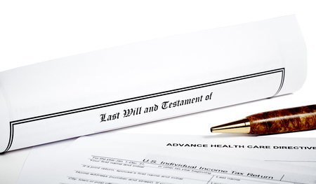 will return: Last Will and Testament rolled up with advance health care directive  and tax returnisolated on white with a pen