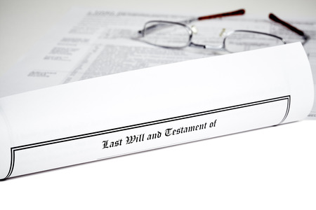 federal tax return: Last Will and Testament rolled up with eye glases and tax form isolated on white with shallow depth of field