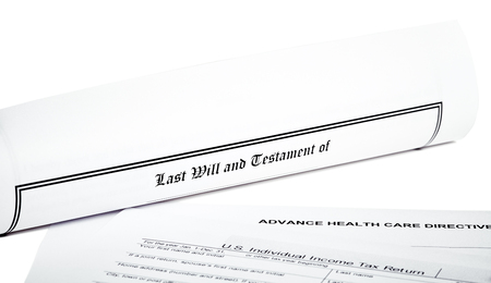 will return: Last Will and Testament rolled up with advance health care directive  and tax return isolated on white Stock Photo