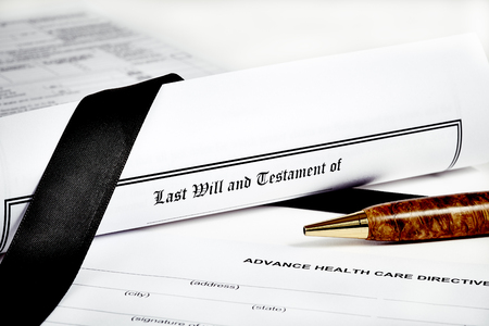 will return: Last Will and Testament rolled up with advance health care directive and tax return in background isolated on white with a pen and black ribbon