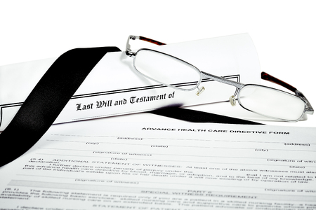 directive: Last Will and Testament rolled up with reading glasses isoated on white with a black ribbon and Advance Health Care Directive Stock Photo