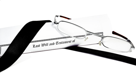 directive: Last Will and Testament rolled up with reading glasses isolated on white with a black ribbon Stock Photo