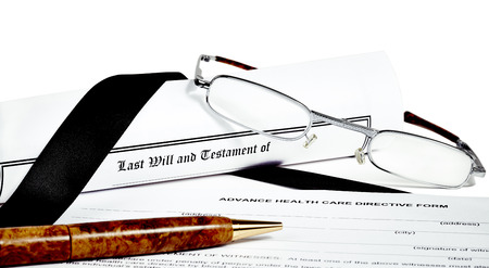 directive: Last Will and Testament rolled up with reading glasses and pen isoated on white with a black ribbon and health care directive Stock Photo