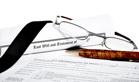 federal tax return: Last Will and Testament rolled up with reading glasses and pen isoated on white with a black ribbon and income tax return