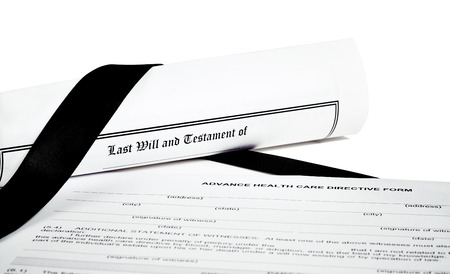 federal tax return: Last Will and Testament rolled up with Health Care Directive and a black ribbon Stock Photo
