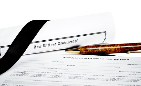 directive: Last Will and Testament rolled up with pen isoated on white with a black ribbon and Advance Health Care Directive Stock Photo