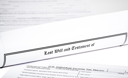 will return: Last Will and Testament rolled up with tax return and  advance health care directive isolated on white shallow depth of field