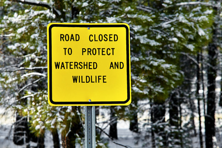 road closed: Road closed to protect watershed and wildlife sign in wilderness with snow