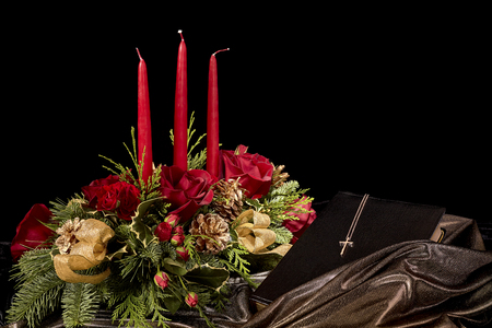 bible flower: Decorative flower arrangement with roses, red candles, gold pine cones, evergreen needles and a cross on a bible isolated on black Stock Photo